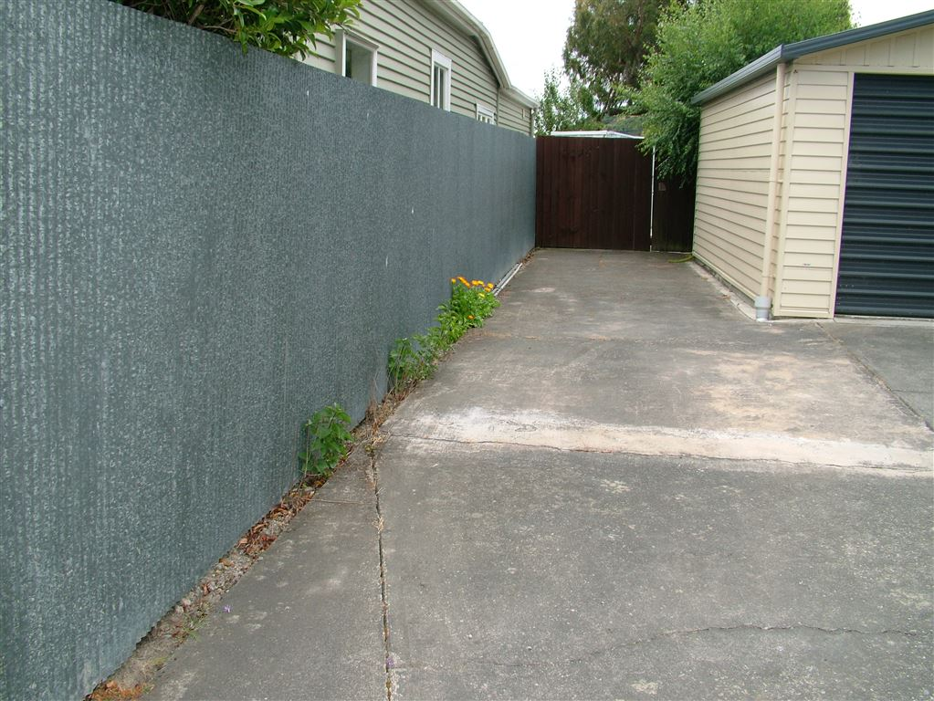 side entrance through a single gate. The garage belongs to the neighbouring property