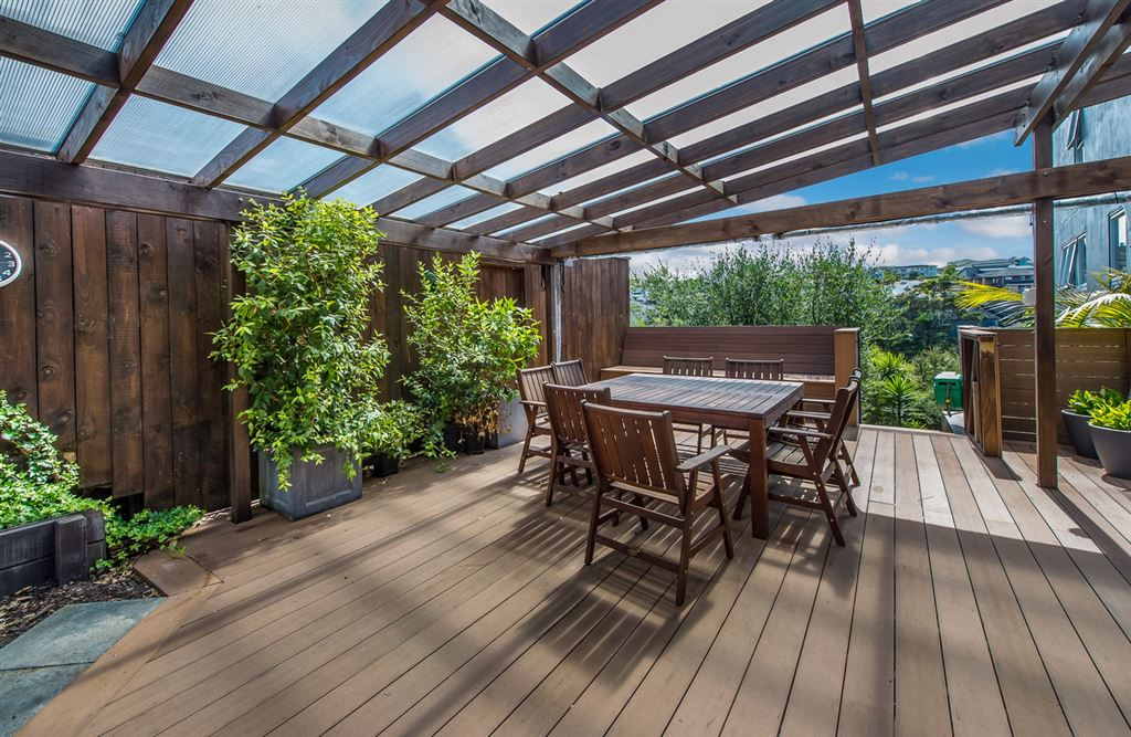 Outside covered deck with bush and urban views